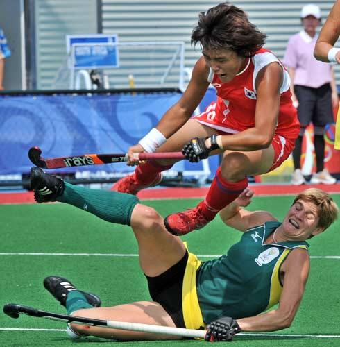 图文-女子曲棍球继续开战 韩国选手跃过南非队员