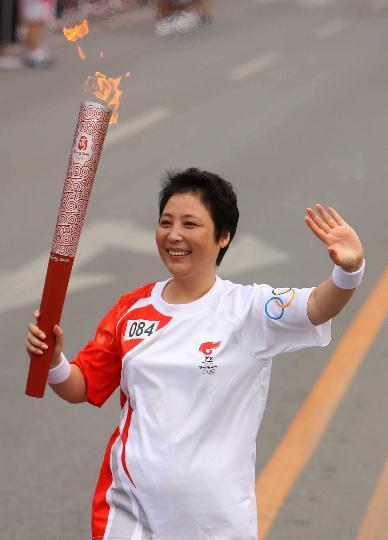 图文-奥运圣火最后一日传递 李桂华手持火炬传递