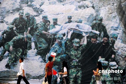 图文-奥运圣火在四川成都传递 抗震宣传画前传递加油