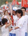 图文-奥运圣火最后一日传递 少先队员向火炬手敬礼