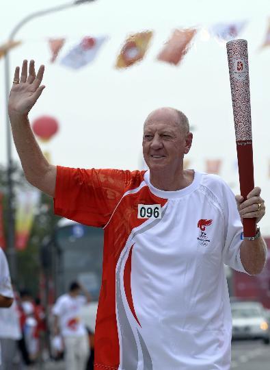 图文-奥运圣火最后一日传递 内维尔手持火炬传递