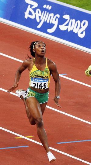 图文-女子100米牙买加选手夺金 箭一样冲过终点