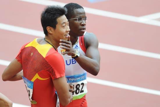 图文-刘翔出战110米栏预赛 罗伯斯与中国选手合影