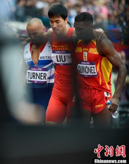 当地时间8月7日,伦敦奥运会110米栏预赛中,刘翔在第六小组第四跑道出赛。但不幸的是起跑之后,刘翔在跨国第一个栏后就摔倒在地。随后,刘翔的右脚无法落地,用一只左脚跑到了终点。两位外国选手过来托住了他,奥组委的官员推来了轮椅。记者 廖攀 摄