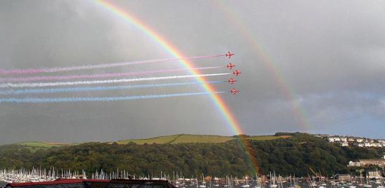 媒体来源:新浪播客 这时,天上出现了一轮壮观的彩虹,飞行拉出的彩色烟雾与彩虹相映成趣。   红箭表演的地点是在英国康沃尔郡,5名飞行员驾驶飞机为每年一度的皇家划船赛助兴,现场有数千人观看。这是红箭第32次为这一赛事表演,飞行时速超过400英里。   但是英国政府有人建议削减红箭的预算,让红箭只拉白烟,这样每年可节省50万英镑。好在一些大臣认为,这样做可能会引发一场公关灾难,因为英国人实在太喜欢这支飞行表演队了,而且自1965年成立后,红箭拉的就是彩烟,世界各地许许多多的人都欣赏过他们的惊险表演:9架飞机每