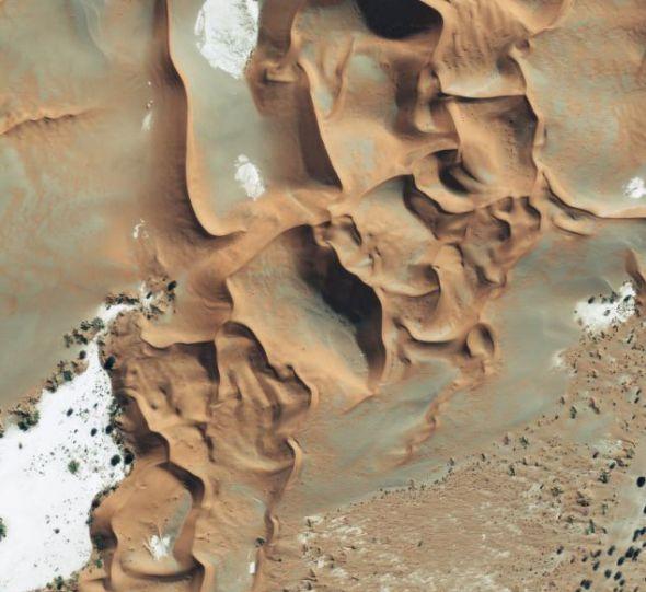 这是安哥拉纳米比亚纳米布沙漠(namib desert)的太空图,在它的中间可以看到世界上最与众不同的一些野生生物和自然保护区。这里有世界上最高的沙丘,它们的高度超过984英尺(299.92米)。过去5500万多年风和沙之间的互动,形成了这种图案精美复杂的辽阔沙漠。