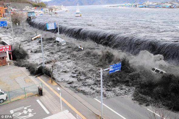 海啸和地震袭击日本后,汹涌而来的海水冲过防洪堤,瞬间淹没黑河入海口附近的一个海滨村庄。