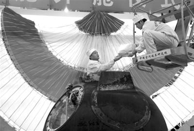 """身着连体白色防静电服的工作人员从返回舱内取出搭载物品。昨日,""""神八""""返回舱开舱仪式在京举行。"""