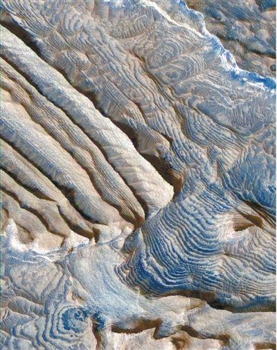 这是美国火星探测器用高分辨率相机拍到的火星沉积岩分层图,看上去有点像地球上的丘陵梯田。
