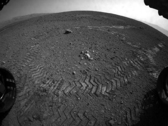 这是好奇号的前部避险相机的鱼眼镜头拍摄的好奇号在火星表面留下的第一段轮胎印迹