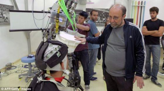 """巴西圣保罗的实验室,尼可莱里斯与他研制的脑控外骨骼。这款外骨骼是国际""""再次行走计划""""的一个研究成果,利用机动化金属支撑结构支撑这名少年的大腿,同时帮助他的大腿弯曲"""