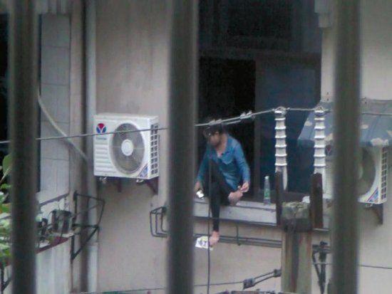 女子坐窗台两个多小时,不时拿起手机看几眼(图片来源:四川新闻网/新浪科技配图)