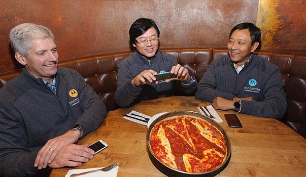 杨元庆在收购完成后很高兴,用手机拍照带有Moto Logo的披萨