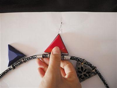 记者尝试用项链挂坠的尖锐处刮纸,纸被划破。本版摄影/新京报记者 王嘉宁