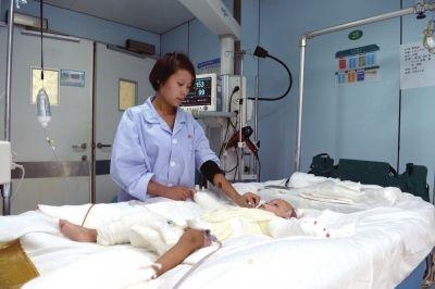 妈妈在病房中照顾烫伤的孩子。京华时报记者 赵思衡 摄