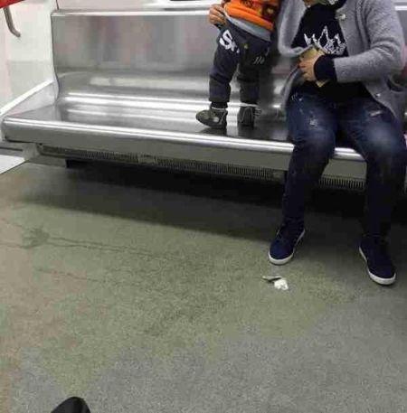 这名年轻妈妈让约两岁大的儿子在一号线上尿尿,让不知情的乘客误踩了。