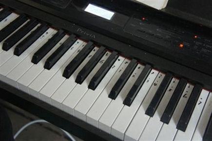 """电子琴的白色琴键上,黑色数字标识着""""哆来咪""""的音符.自学成才的"""