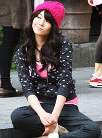 在街头席地而坐的俏皮姑娘