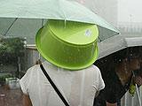 暴雨中行人顶着塑料盆