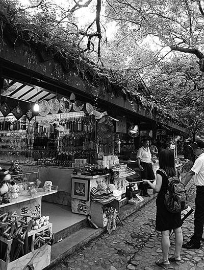 在福建武夷山某景区旅游商店,几位游客正在挑选旅游纪念品。遗憾的是在琳琅满目的旅游商品中,真正富有当地特色的旅游纪念品却难以寻觅。本报记者顾阳摄