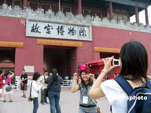 """资料图:2005年7月13日,参加第五届""""湖湘文化之旅""""、来自台湾36所大学的100余名台湾青年学子,在北京故宫博物院参观。图为一台湾女生在故宫神武门前戴起宫廷帽拍照留念。"""