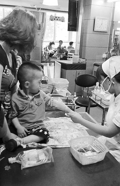 """5月21日,济南市中心医院儿科护士在给患儿抽血时未做到""""一人一带""""。 王照重/摄"""