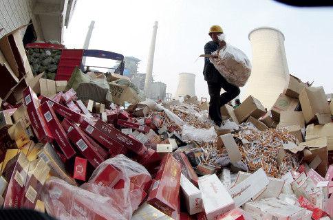 """2014 年""""3·15""""前夕,河南省許昌市,工人將假冒偽劣香煙傾倒在焚燒爐旁,準備用於燃燒發電。CFP"""