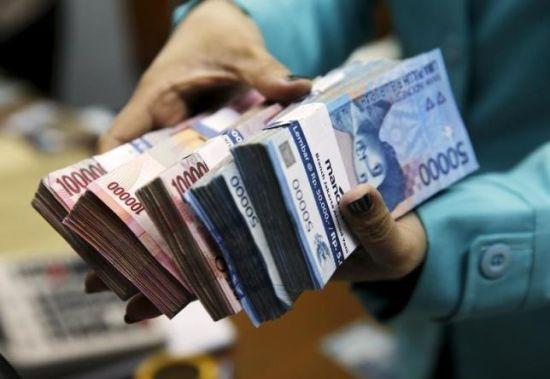图为印尼首都雅加达的一个货币兑换处,一名女子拿着印尼卢比现钞。 (Reuters)