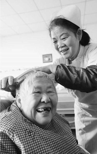 河南省开封市养老院服务人员正在给老人梳头。   李俊生摄