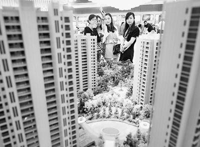 图为近日,浙江杭州一家房产公司的两位销售人员一起向购房者介绍楼盘。新华社记者 王定昶摄