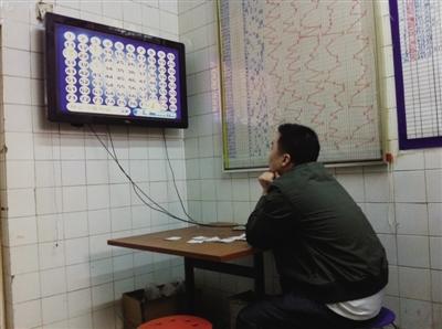 4月27日,一名彩民正在聚精会神看开奖。