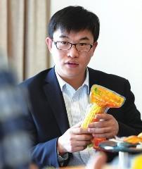 """3月10日,全国人大代表马瑞强在向记者介绍他的""""水果玉米""""。王建华/摄"""