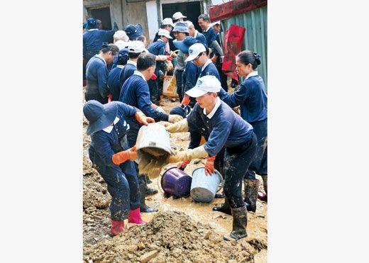 """2010 年10 月25 日,台风""""鲇鱼""""过后,在台湾宜兰县赈灾现场,慈济的义工们协助受灾民众打扫家园"""
