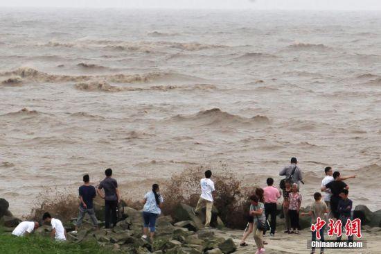 7月10日,超强台风台风 灿鸿 来袭,受其影响,上海中心气象台当日发布台风黄色预警信号,预计10日晚下半夜至11日中午在福建到浙江一带沿海登陆,大风暴雨将袭上海,最大阵风可达8-9级,长江口区及沿江沿海地区可达10-11级。但在上海浦东某观海堤坝上,仍有不少市民不顾危险翻越警戒线,追逐涌起的浪花,场面险象环生。中新社发 张亨伟 摄