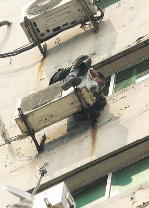 拖着残腿爬上高层空调室外机