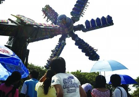 """23日,在中山公园欢动世界游乐场内,游客们争相排队乘坐游乐项目"""""""