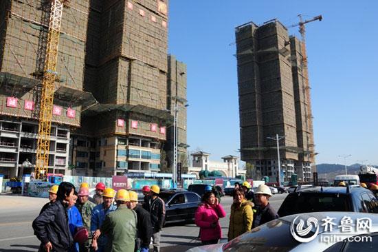 很多工人都跑到了建筑工地对面马路上。