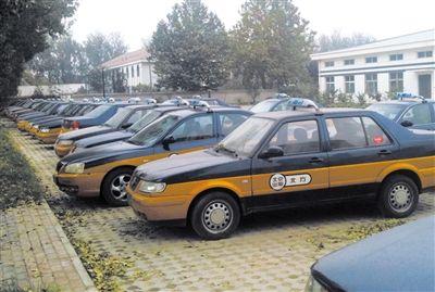 前日,一出租车公司院内停放着闲置的出租车。