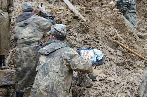 """救援人员从彝良县龙海乡""""10·4""""山体滑坡灾害现场挖出来的遇难学生书包。记者赵文瑞 摄"""