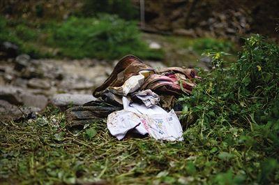 10月8日,从废墟中挖出的书包和书本遗落在废墟边的草丛中。