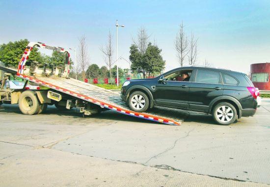 昨日,绕城高速,一辆牌照过期、也没年审的车被拖走 摄影记者 刘畅