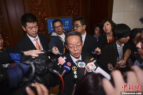 2012年11月9日,十八大中央国家机关代表团在北京人民大会堂讨论大会报告,并对中外媒体开放。图为港澳记者在门前围堵十八大代表、港澳办主任王光亚。中新社发 廖攀 摄