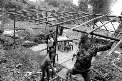 22日,天全县始阳镇乐坝村的村民就地取材用竹子搭建帐篷。 新华社发