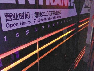 """昨晚,李某案发前曾去的酒吧贴着""""未成年人禁入""""的标识,酒吧人员称该标识已挂了一年多。新京报记者 石明磊 摄"""