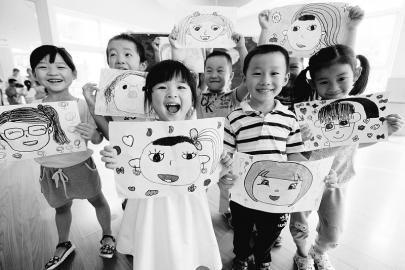"""小朋友们在展示老师""""笑脸""""的绘画作品"""