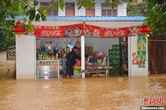 """11月11日,雨水积涝浸入广西浦北县小江镇东风街的一家个体商店。当天上午,第30号台风""""海燕""""进入广西境内,广西多地遭受强风暴雨袭击,造成部分道路毁损,部分街道积涝严重,居民房屋受淹,沿海部分地区降雨量逾200毫米。中新社发 邓昌平 摄"""