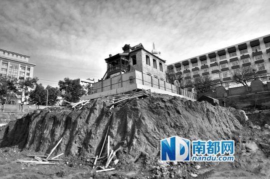 古建筑孤独矗立在一个土堆上,四周被挖空。来源:人民网