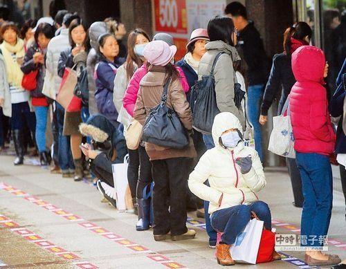 适逢百货公司周年庆,民众不畏寒流,一早就在百货公司外排队。图片来源:《中国时报》