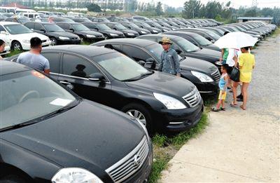 昨日,市民在山东枣庄一家拍卖公司场地上查看待拍卖公车。当日,枣庄市103辆公车公开拍卖。新华社记者 冯杰 摄