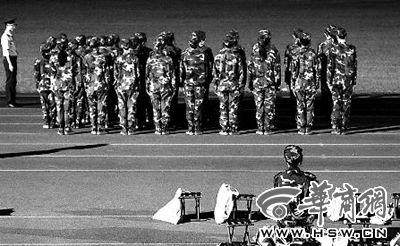 8月27日,西安交通大学兴庆校区大一新生正在进行军训,一位身体不适的女生在场边休息 华商报记者 张杰 摄